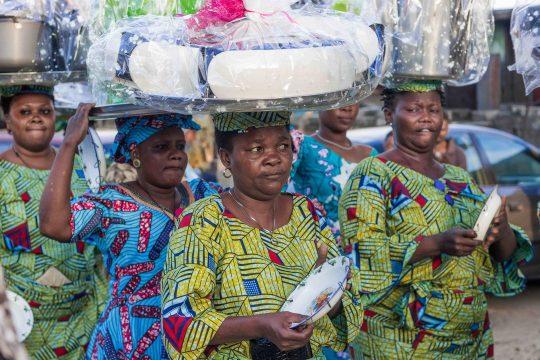Un groupe de femmes portant sur leurs têtes des cadeaux emballés.