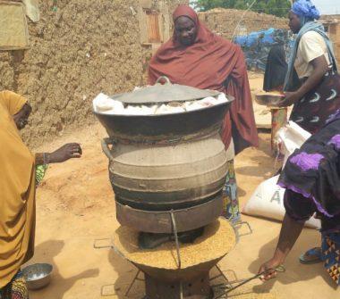 Des femmes préparant sur un four à balle de riz