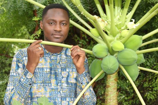 Souleymane Tamponé tenant une branche de papayer / Crédit photo : Be Proud